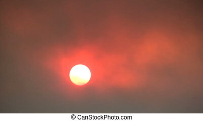 Wildfire Smoke and Red Sun - a red sun poking through thick...