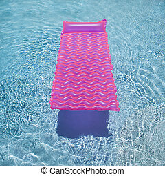 Pink float in pool. - Pink lounge float in empty swimming...