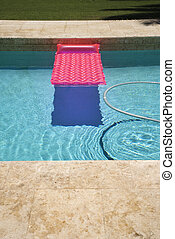 Pink float in pool. - Pink float and vacuum hose in swimming...