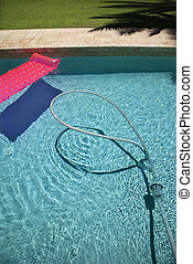 Float and vacuum in pool. - Pink float and vacuum hose in...