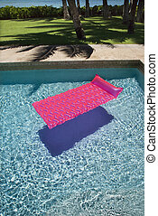 Float in swimming pool. - Pink float in empty swimming pool.