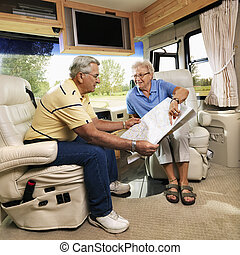 Senior couple in RV. - Senior couple sitting in RV looking...