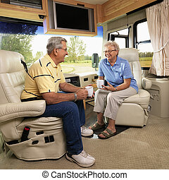 Senior couple in RV. - Senior couple sitting in RV holding...