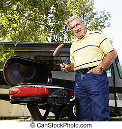 Senior man grilling by RV. - Senior adult man grilling...