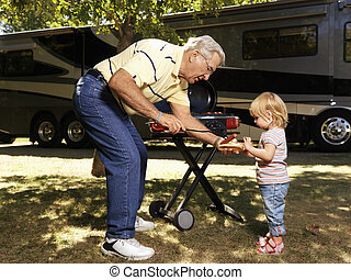 Man and child with hotdog - Grandfather giving granddaughter...