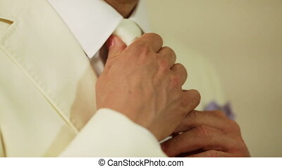 Morning groom - Groom tightens tie. Groomsman helps him and...