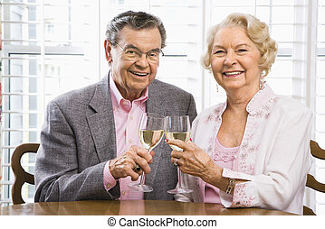 Mature couple with wine - Mature Caucasian couple toasting...