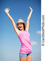 girl with hands up on the beach - summer holidays and...