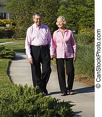Mature couple walking - Mature Caucasian couple walking down...