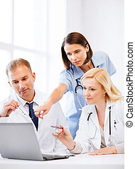 doctors looking at laptop on meeting - healthcare, medical...