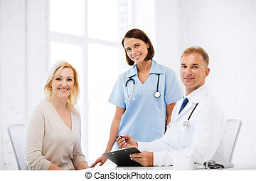 doctor and nurse with patient in hospital - healthcare and...