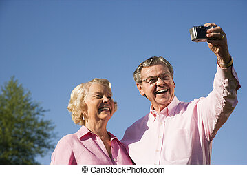 Mature couple taking picture - Mature Caucasian couple...