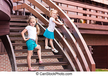 Two cute happy gilrs outdoor on stairs