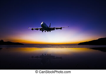 Airplane flying on tropical colorful evening sky over the...