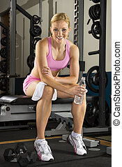 Woman on weight bench. - Caucasian mid-adult woman sitting...