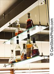 Liquor bottles. - Glass shelves with liquor bottles.