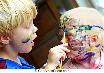 Child Painting his Baby Brother's Face - a Small child is...