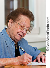 Senior writes a letter - Old woman writes a letter