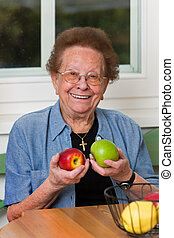 Senior with fruit for vitamins - Old woman with apple for...