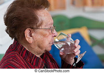 Senior drinking water from a glass - Old woman drinking...