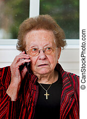 Senior leads with phone call - Old woman carries a telephone...