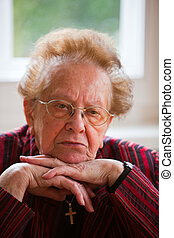 Pensive senior - An old woman sits thoughtfully at the...