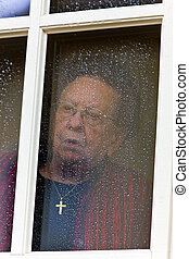 pensive senior looks sad from a window - Old woman at the...