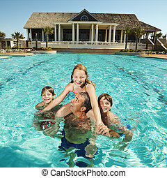Family at pool. - Caucasian family at pool with clubhouse in...