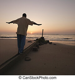 Man on sand barrier - African American male balancing on...