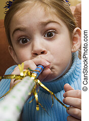Girl blowing noisemaker - Caucasian girl blowing noisemaker...