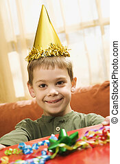 Boy holding birthday gift - Caucasian boy wearing party hat...