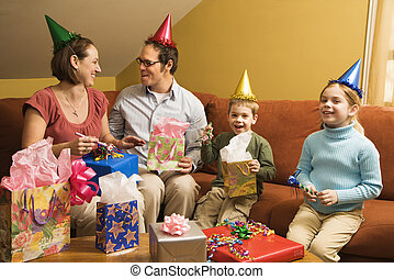 Family birthday party - Caucasian family wearing party hats...