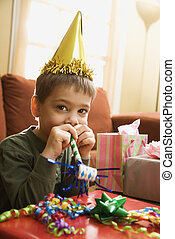 Boy blowing noisemaker. - Caucasian boy at birthday party...