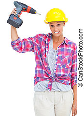 Attractive handy woman holding a power drill on white...