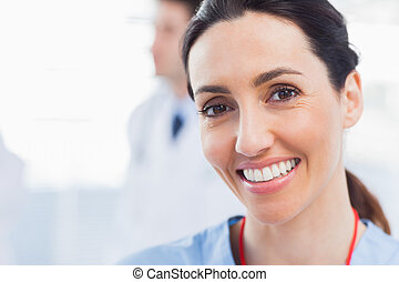 Smiling nurse looking at camera with a doctor behind her in...