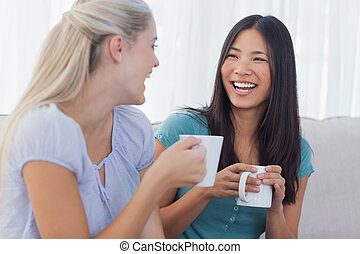 Young friends catching up over cups of coffee at home on...