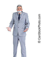 Businessman gagged with adhesive tape on mouth on white...
