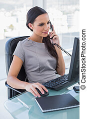 Concentrated businesswoman answering phone and working on...