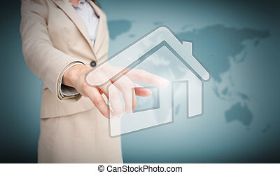 Businesswoman touching house graphic on world map background