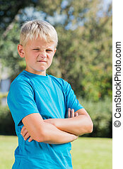 Young boy looking angry with crossed arms in the park...