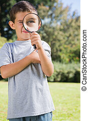 Small child looking through a magnifying glass - Small child...