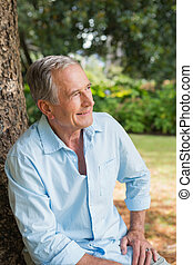Thoughtful retired man sitting on tree trunk