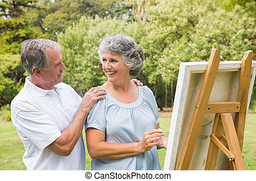Happy retired woman painting on canvas with husband in the...