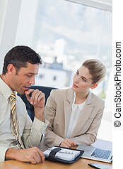 Businessman consulting his agenda while talking to his colleague in his office