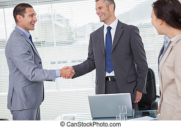 Smiling businessmen standing and shaking hands