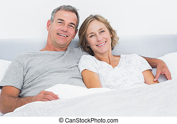 Happy couple cuddling in bed looking at camera at home in...