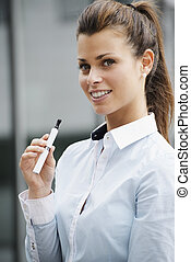 portrait of young woman smoking electronic cigarette -...