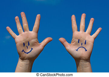 Hands with smiles and sadness pattern against the blue sky