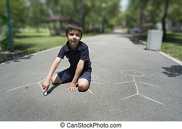 Child drawing family on asphalt in a park