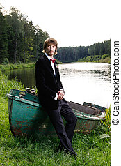 Beautiful young groom sitting on boat on the lake